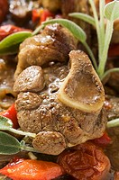 Osso buco with tomatoes and sage close-up