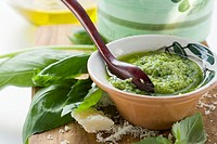 Pesto with olive oil in small bowl, basil, Parmesan