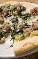 Pizza with tuna, chard and olives, a slice taken