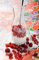 Fresh berries with sugar in carafe with spoon