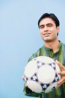 Portrait of a young man holding a soccer ball and smiling