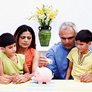 Mid adult man putting an Indian currency note into a piggybank with his wife and two sons beside him