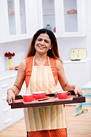 Portrait of a mid adult woman holding a serving tray and smiling in the kitchen