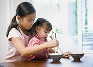 Asian girl helping sister use chopsticks