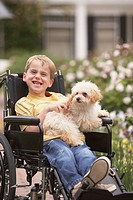 Young boy in wheelchair smiling and holding dog (thumbnail)