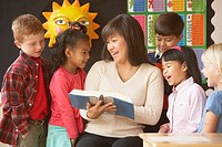 Asian female teacher reading to students