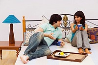 Young couple sitting on the bed and holding mugs of coffee