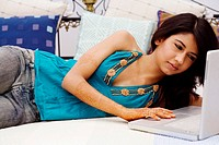 Young woman lying on the bed and using a laptop