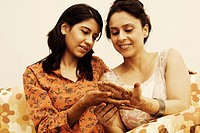 Two women looking at their henna tattooed hands