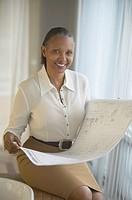 Senior African businesswoman holding blueprints