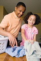 African father and daughter folding laundry