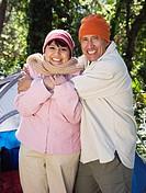 Senior couple hugging next to tent