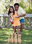 Hispanic father helping daughter play lawn bowling