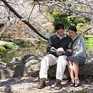Asian couple looking at guide book in park