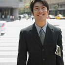 Asian businessman smiling in urban area