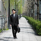 Asian businessman walking on sidewalk with briefcase