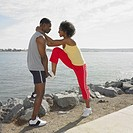 African couple in athletic gear stretching outdoors