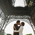 Couple kissing under Eiffel Tower
