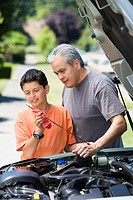 Hispanic father and son checking oil in car
