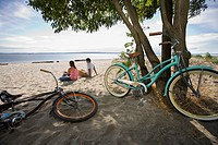 Pacific Islander couple sitting on beach with bicycles