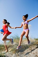 Two Hispanic girls running down sand dune