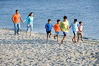 Hispanic family walking on beach