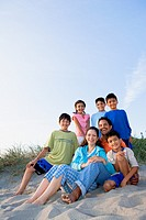 Portrait of Hispanic family sitting on beach
