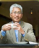 Senior Asian businessman holding cup of coffee