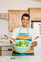 Indian man holding bowl of salad in kitchen