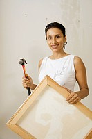 Indian woman holding picture and hammer