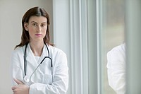 Female doctor standing next to window indoors