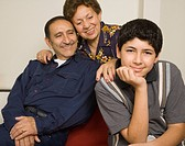 Hispanic grandparents and grandson smiling indoors