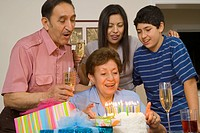 Multi-generational Hispanic family with birthday cake