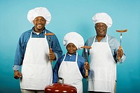 Multi-generational African male family members with barbeque grill