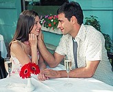Hispanic couple smiling at each other at outdoor cafe