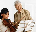 Senior Asian woman teaching young Asian girl violin