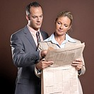 Businessman and businesswoman, holding newspaper