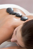 Young woman receiving hot stone massage, close-up