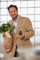 Man standing in kitchen, holding paper bag and wine bottle, smiling