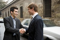 Two Hispanic businessmen shaking hands in street
