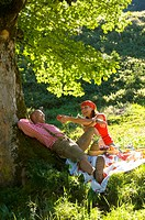 Couple having picnic under tree