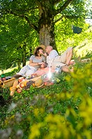 Couple having picnic under tree, kissing