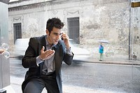 Hispanic businessman talking on cell phone next to window