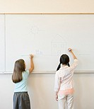 Two young girls drawing on whiteboard in classroom