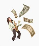 Studio shot of woman playing saxophone with dollar bills coming out