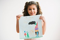 Young Hispanic girl holding up drawing