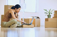 Asian woman using laptop in new house with boxes