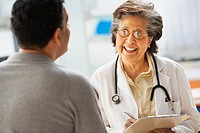 Senior Hispanic female doctor talking to patient