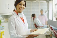 Indian female dentist holding chart and smiling