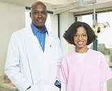 African male dentist with African female dental assistant smiling
